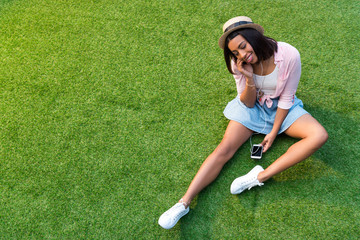 smiling young african american woman in earphones listening music with smartphone while sitting on lawn