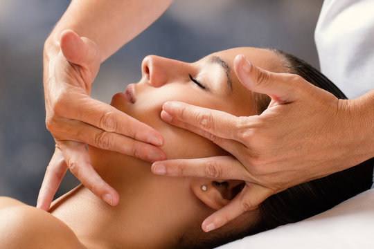 Therapist massaging female face.