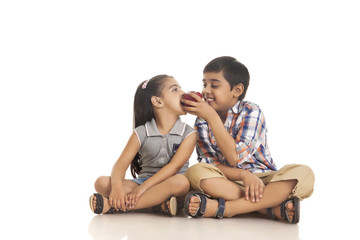 Full length of brother feeding apple to sister while sitting against white background
