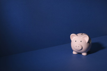 Smiling Piggy Bank Over Blue Background Copy Space