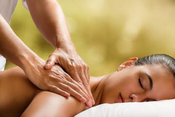 Young woman enjoying massage in spa.