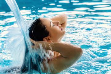 Young woman enjoying water cascade in spa.