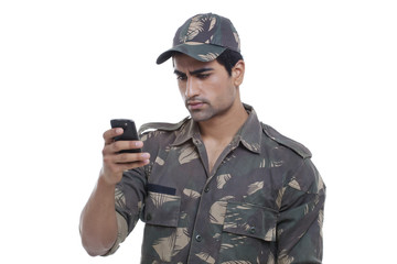 Serious young soldier reading message on his cell phone