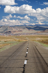 Empty Asphalt road in Mongolia  with mongolian town Bayan-Olgii (Bayan-Ulgii or Ulgii) on background