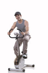 Portrait of a young man on exercise bike over white background