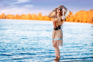 A young woman in a traditional Indian costume and a rouce on her head, stands in the river