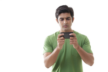 Serious young man reading text message over white background