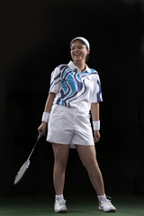Full length of happy female player holding badminton racket isolated over black background
