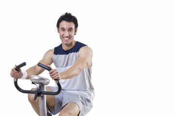 Portrait of a happy young man on exercise bike over white background