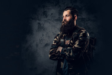 Bearded tattooed male in camouflage jacket.