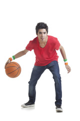 Full length portrait of young boy playing basketball over white background
