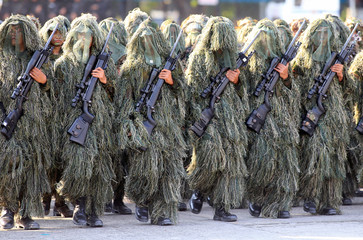 A sniper squad of the Philippine National Police (PNP) in camouflage outfits march during the 116th Police Service Anniversary inside the Philippine National Police (PNP) headquarters in Quezon city, metro Manila