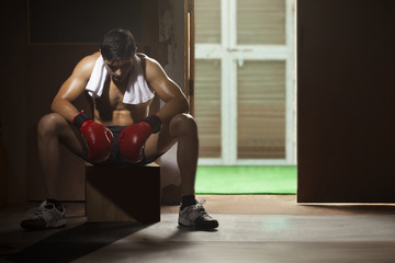 Tired young male boxer sitting on stool in gym