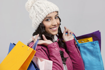 Close-up portrait of young woman holding shopping bags