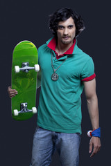Portrait of a funky young man holding skateboard against black background