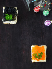 Canape with red and black caviar and wine glasses with Christmas decorations in the background