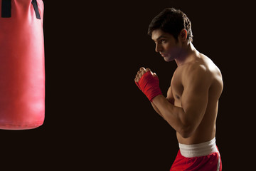 Side view of young male boxer looking at red punching bag over black background