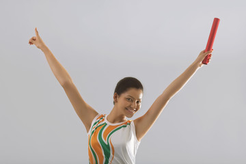 Portrait of female relay runner celebrating victory isolated over gray background