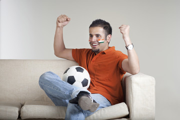 Happy young man with soccer ball cheering while sitting on sofa