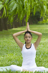 Young woman doing yoga with hands in prayer position