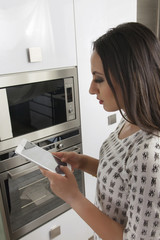 Young woman using mobile phone in front of oven in the kitchen