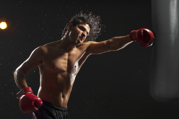 Boxer hitting punching bag over black background