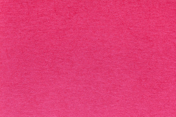 Texture of old bright red paper background, closeup. Structure of dense magenta cardboard