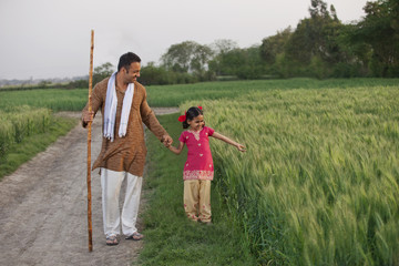 Full length of little girl with her father in a wheat field