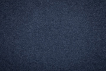 Texture of old navy blue paper background, closeup. Structure of dense dark denim cardboard