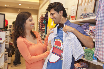 Happy couple shopping together in clothing store