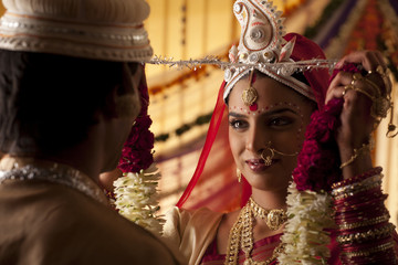 Bengali bride putting a garland on groom