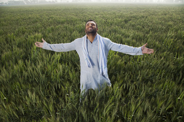 Indian man standing in field with arms out