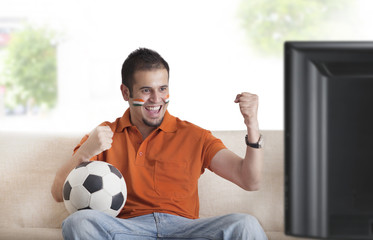 Excited young man with painted face cheering while watching soccer game on television