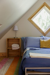 USA, Maine. Bed room in the attic of a design cabin, with a tilted square window.