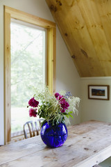 USA, Farmington, Maine. A purple vase with a bouquet of flowers on a wooden table in a cabin with wooden ceilings.