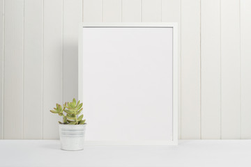White picture frame with green plant on white wooden panel background with white desk