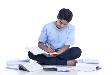 Smiling teenage boy sitting on floor cross-legged studying against white background