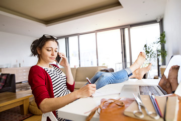 Woman on the phone working at desk at home