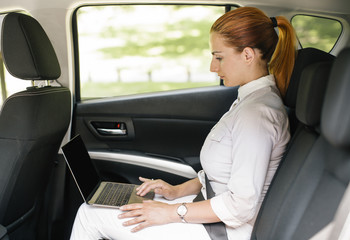 Businesswoman sitting on backseat of a car using laptop