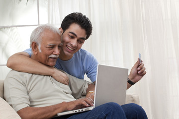 Grandson teaching grandfather how to operate laptop