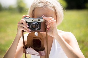 Young blond female making photo shots by vintage camera. Woman outdoors taking pictures of her daughter.