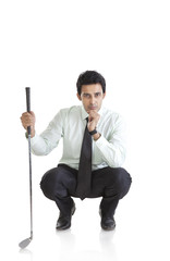 Portrait of business executive with golf club thinking
