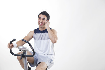 Young man exercising while talking on cell phone over white background