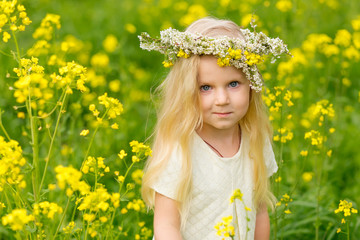 Beautiful little girl with a wreath on her head playing in a flowering field.