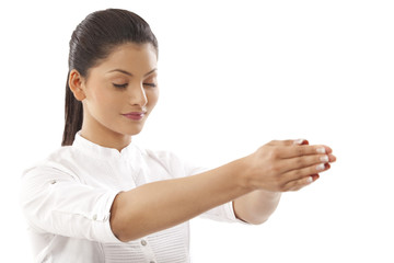 Close-up of woman with hands clasped and eyes closed doing yoga over white background