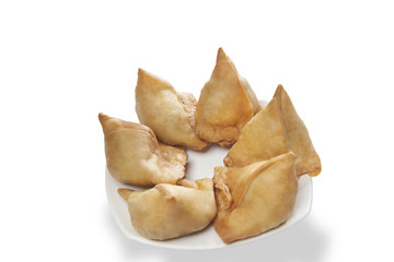 Close-up of plate full of samosas over white background