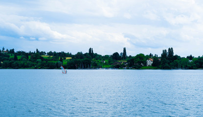 A sailboat with a man on the Lake Bodensee in Germany. Wall mural