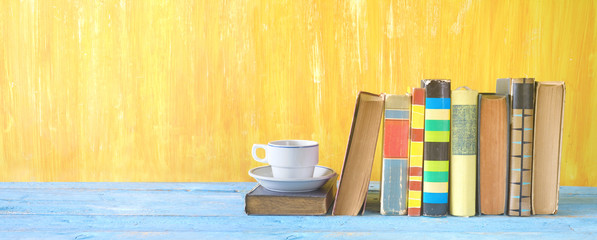 old books in a row and a cup of coffee,, panorama, free copy space