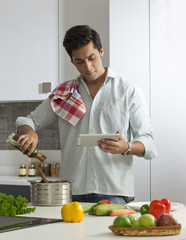 Man cooking using a digital tablet for recipes