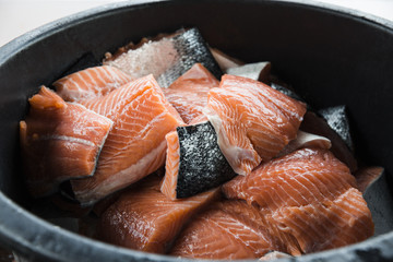 Bucket full of fresh cut salmon fillets with skin
